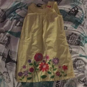 A yellow child dress with flowers at the bottom